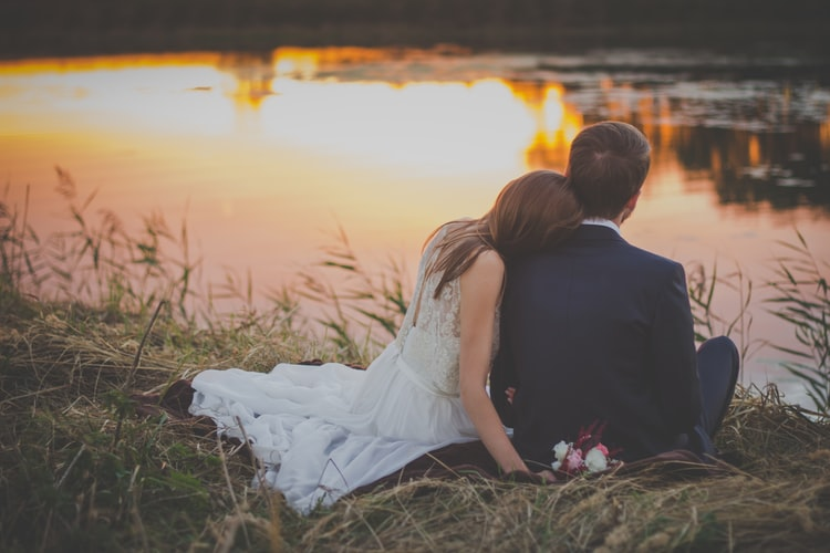 Bride and Groom Sitting on the Edge of a Lake