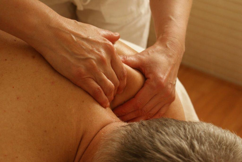Person massaging the old man's shoulder - Stress Relief Activities | Blurbgeek