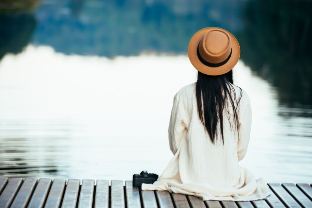 Girl relaxing on waterfront raft - Stress Relief Activities | Blurbgeek