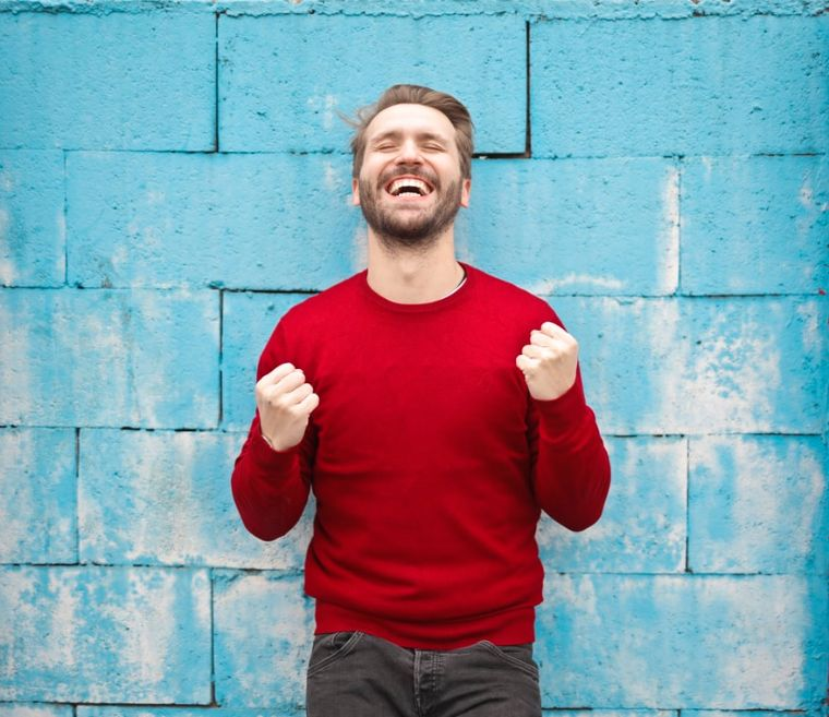 A happy man standing in-front of the wall | Stress Relief Activities | Blurbgeek