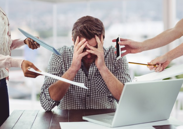 A man sitting in his office with excessive stress on him | Blurbgeek