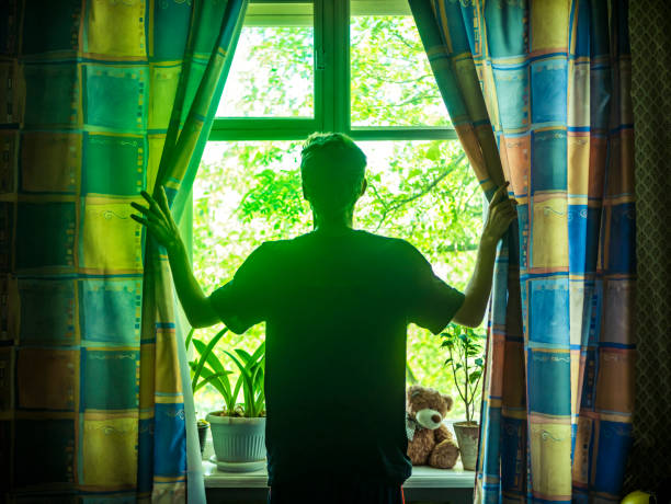 Young man opens curtains on the window on the sunny summer morning - 5 Motivational Things   Blurbgeek